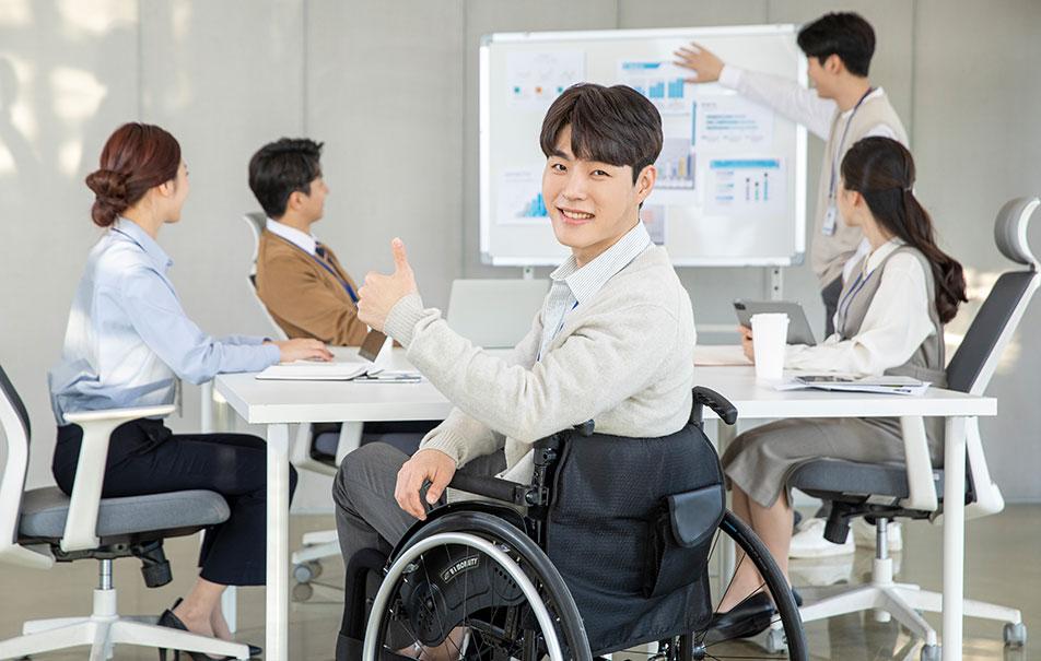 휠체어를 탄 남자가 엄지를 올리고 있는 이미지