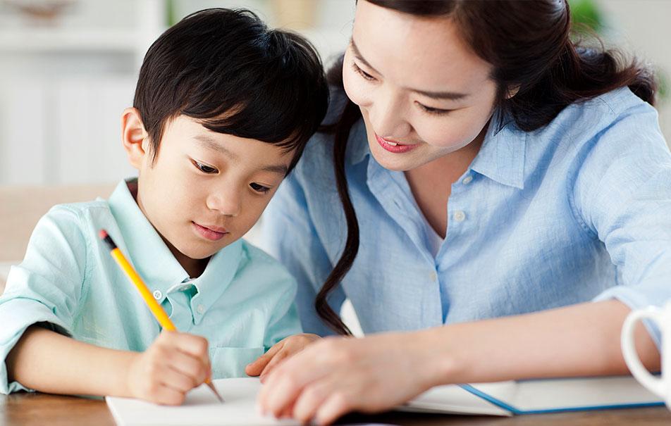 여자선생님이 남자아이의 학습을 지도하는 이미지